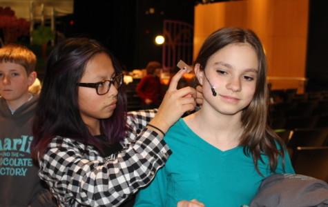 Eighth grade student director Glendy Cirolia carefully attaches a mic setup to 6th grade actor Natasha Taubenheim.