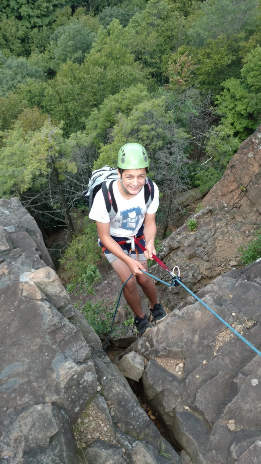 Above, an 8th grader repelling down a rock face in Kent, Connecticut.
