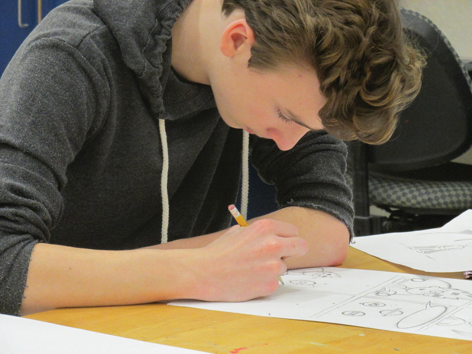 An 8th grade student sketches his comic design.