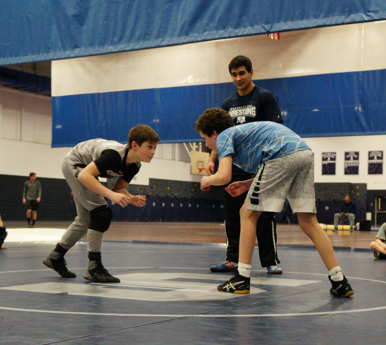 Charlie Iannone and another student wrestle under the watchful eye of P.A.L. Wrestling Coach Pallo.