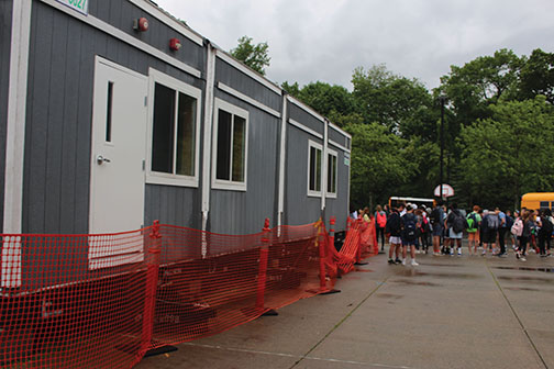 Arrival of the portable classrooms in the bus loop and off of the gym is part of the preparations for the next school year.