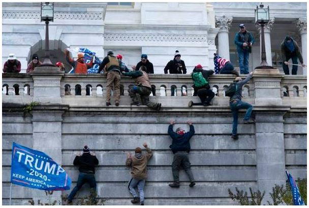 Protesters+climb+up+in+order+to+try+to+illegally+enter+the+capitol+building.%0A