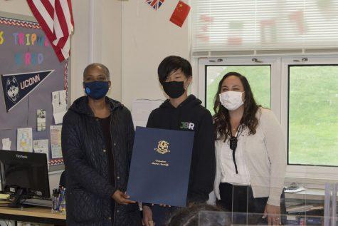 Representative Stephanie Thomas gives an 8th grade writer a award with his social studies  teacher Gabrielle Tripuzzi.