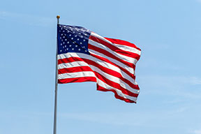 American flag waving on pole with bright vibrant red white and blue colors, negative space